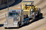 a semi-truck hauling heavy construction equipment