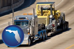 florida map icon and a semi-truck hauling heavy construction equipment
