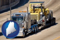 maine map icon and a semi-truck hauling heavy construction equipment