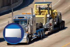 south-dakota map icon and a semi-truck hauling heavy construction equipment