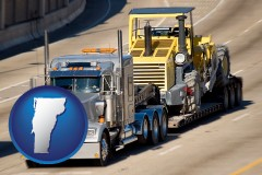 vermont map icon and a semi-truck hauling heavy construction equipment