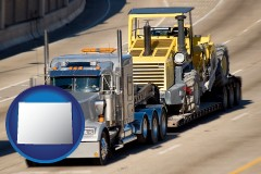 wyoming map icon and a semi-truck hauling heavy construction equipment